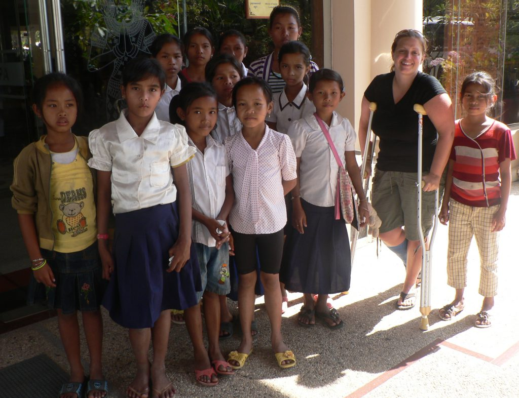 Image with children in Cambodia and woman on crutches is Nicky, and the beach shot from left to right is: Rachele Wilson, volunteer Sam Hancock, CEO Nicky Mih, Zakiya Willcocks-Okoth (Sam W daughter), Sam Willcocks, and volunteer Megan Macholf.